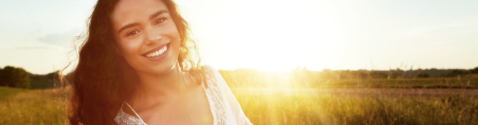 smiling woman standing in front of a beautiful sunrise