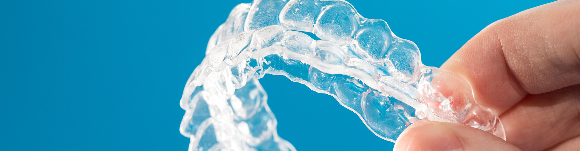 closeup of a person holding a set of Invisalign clear aligners