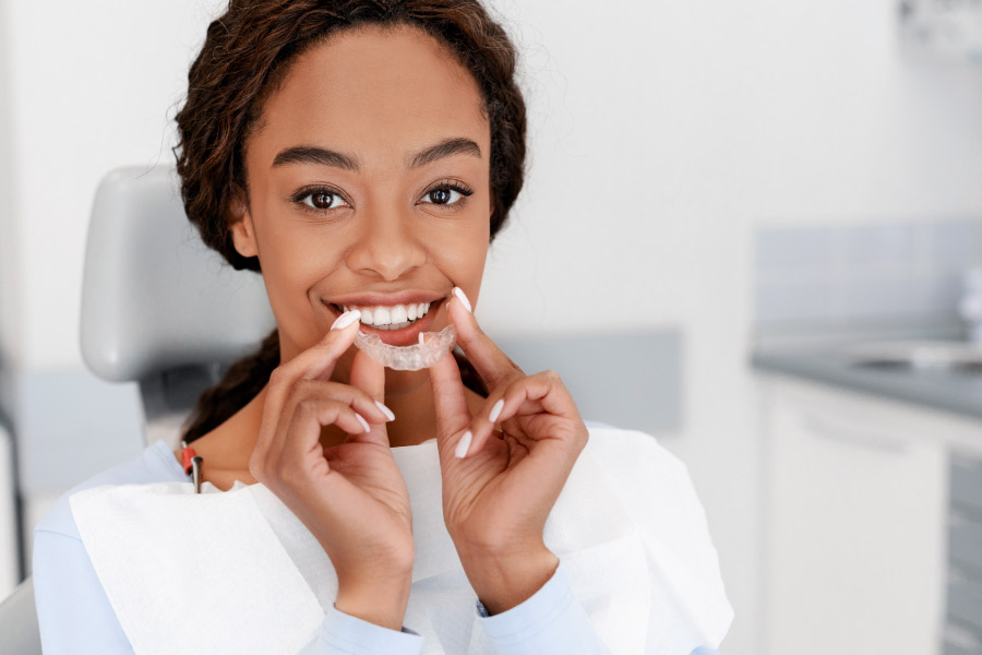 Pretty black girl at the dental office holding a clear aligner in front of her smile.