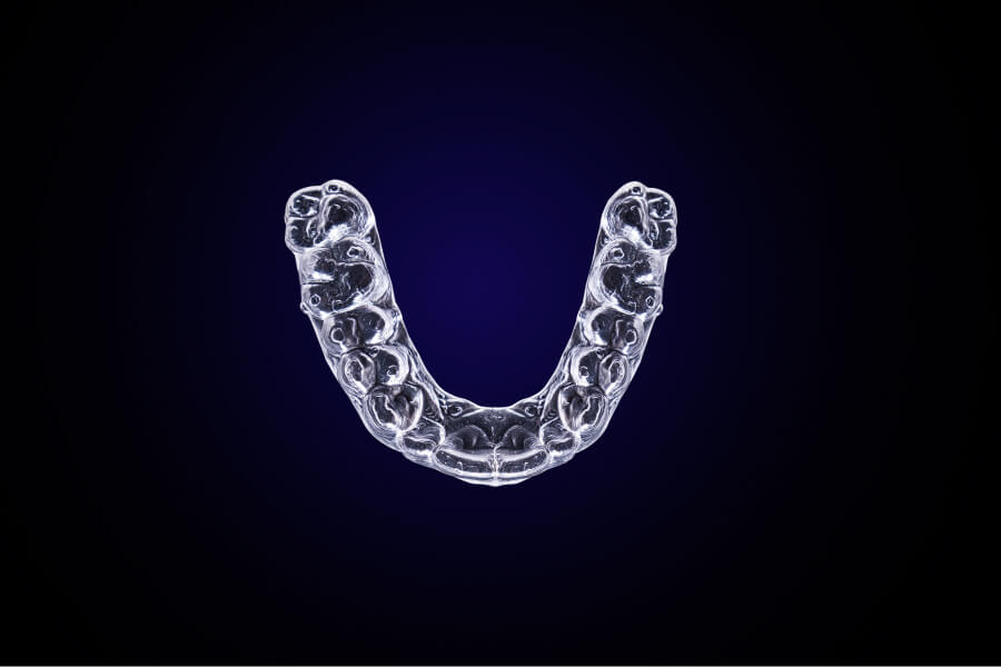 Aerial view of clear aligners on a navy blue background for a blog post about how to clean them
